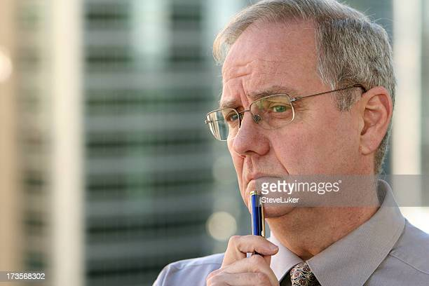 Man with pen thinking.