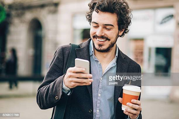 Man with phone and cofee outdoors in the city