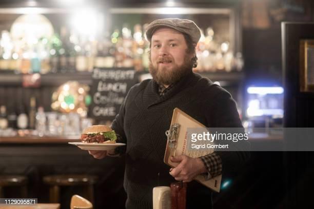 man with plate of burger and menu in pub - sigrid gombert imagens e fotografias de stock