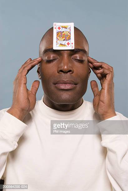 Man with playing card on forehead, eyes closed