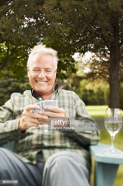 Man with playing cards and white wine