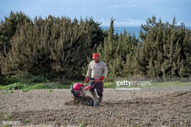 man with ploughing machine working on the field. - emreturanphoto stock pictures, royalty-free photos & images