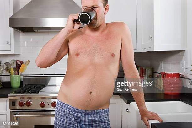Man with pot belly drinking coffee