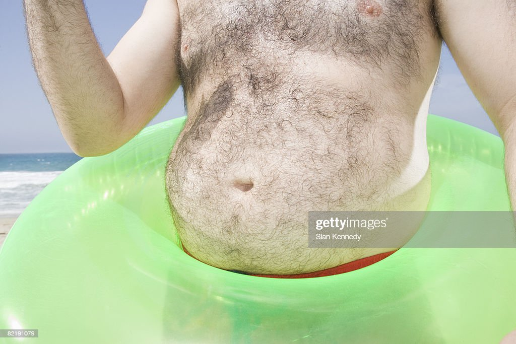 Man with pot belly on the beach : Stock Photo