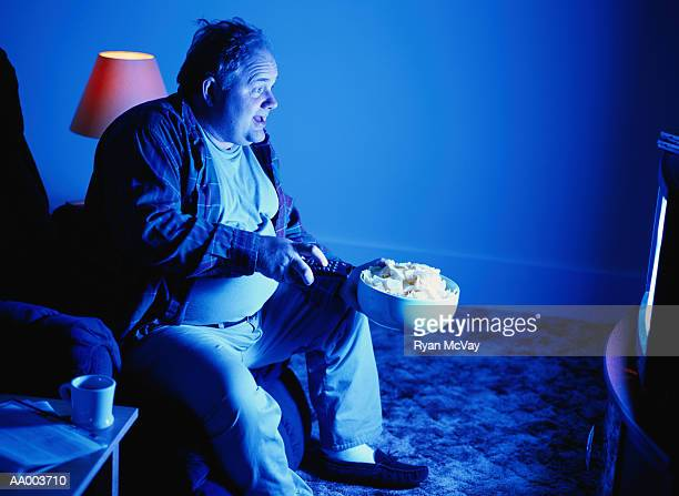 Man with Potato Chips and a Remote Control