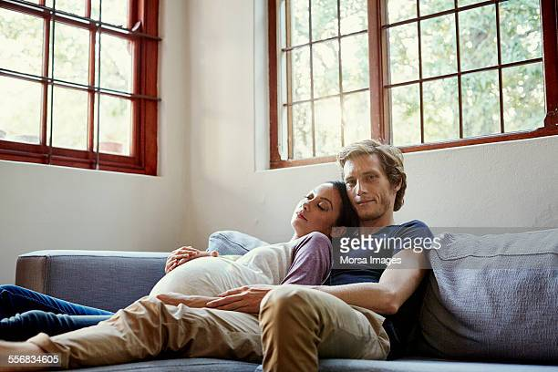 Man with pregnant woman sleeping on sofa