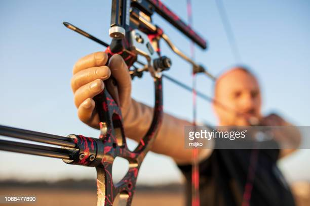 man with prosthetic arm doing archery outdoors - archery stock pictures, royalty-free photos & images