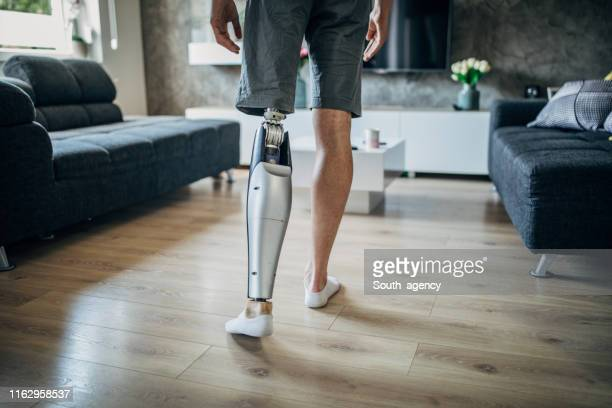 man with prosthetic leg at home - artificial limb stock pictures, royalty-free photos & images