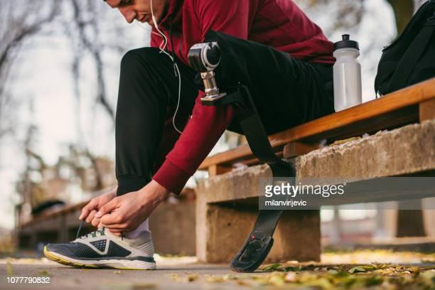 Man with prosthetic leg make preparation for running