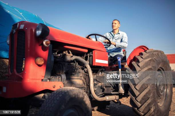 Man with prosthetic leg on tractor at farm