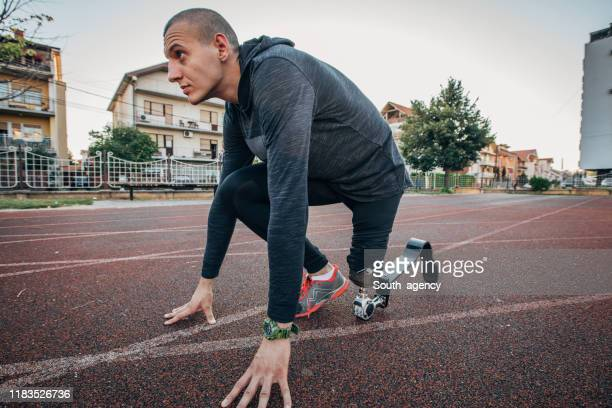 man with prosthetic leg preparing for training - men's track stock pictures, royalty-free photos & images