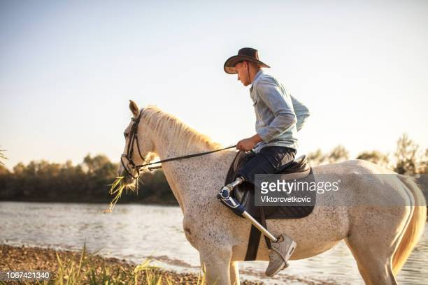 man with prosthetic leg ride a horse at ranch. - animals in the wild stock pictures, royalty-free photos & images