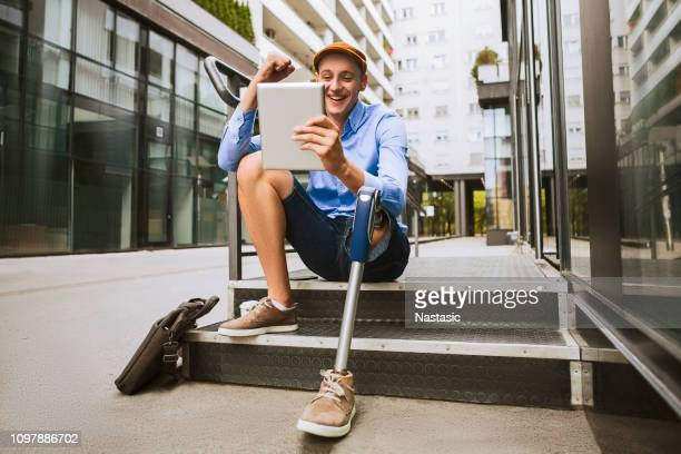 man with prosthetic leg sitting in front of the office building while talking on a digital tablet - physical disability stock pictures, royalty-free photos & images