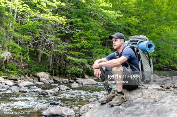 Man with prosthetic leg sitting on rock by the river