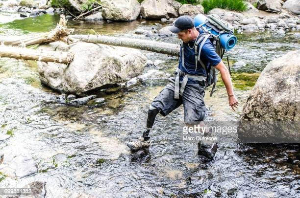 Man with prosthetic leg walking on rocks to cross a river
