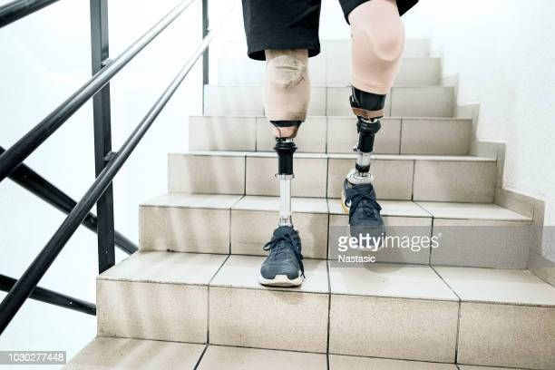 man with prosthetic legs going down the stairs - paraplegic stock photos and pictures