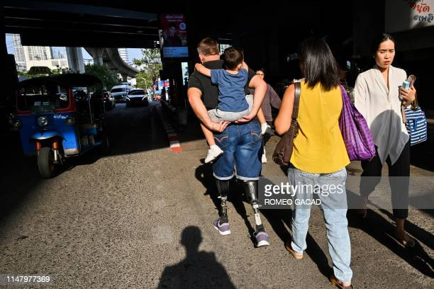 A man with prosthetics legs carries a child on his back while followed by a woman as they walk along a street in Bangkok on June 4 2019