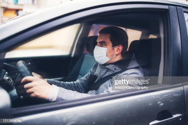 man with protective face mask driving the car - driving mask stock pictures, royalty-free photos & images