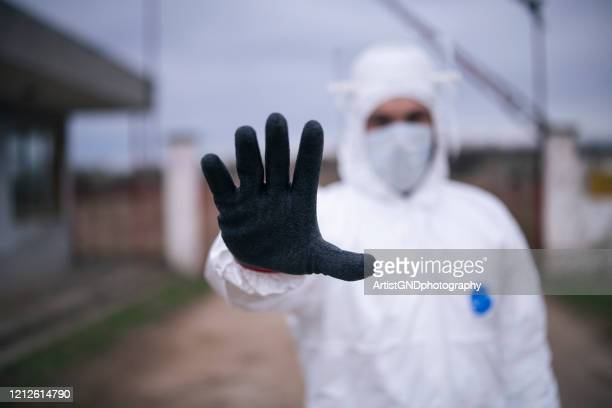 man with protective suit controlling border traffic,close border crossing virus pandemic - illness prevention stock pictures, royalty-free photos & images