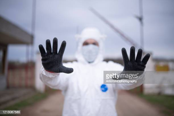 man with protective suit controlling border traffic,close border crossing virus pandemic - national border stock pictures, royalty-free photos & images