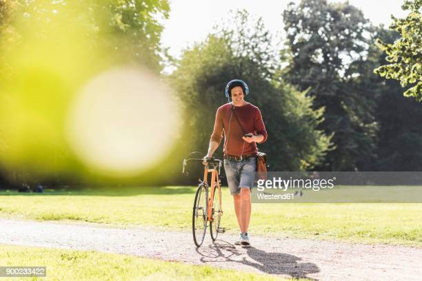 Man with racing cycle listening music with headphones in a park