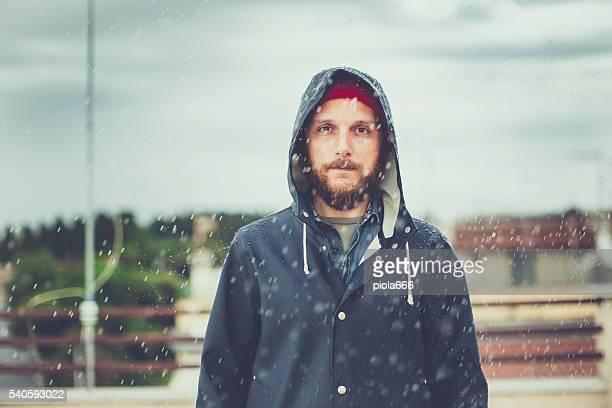 Mann mit Regenmantel unter starkem Regen