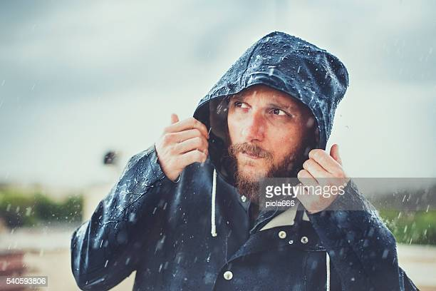 Man with raincoat under heavy rain