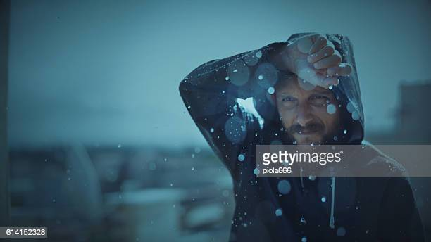 man with raincoat under storm and heavy rain - heavy rain stockfoto's en -beelden