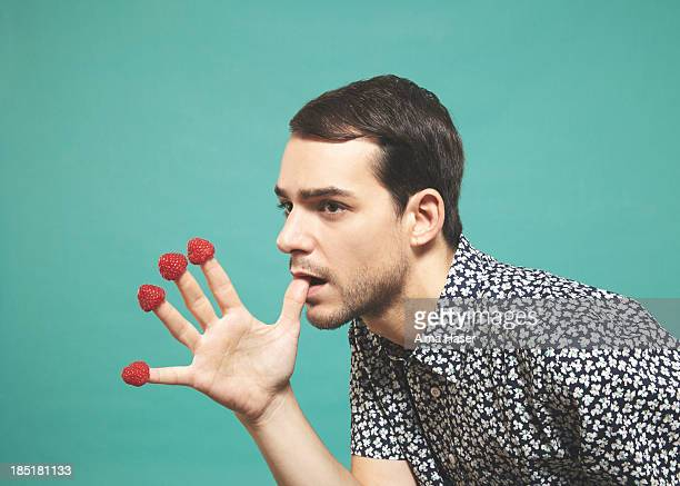 Man with raspberries  on finger tips