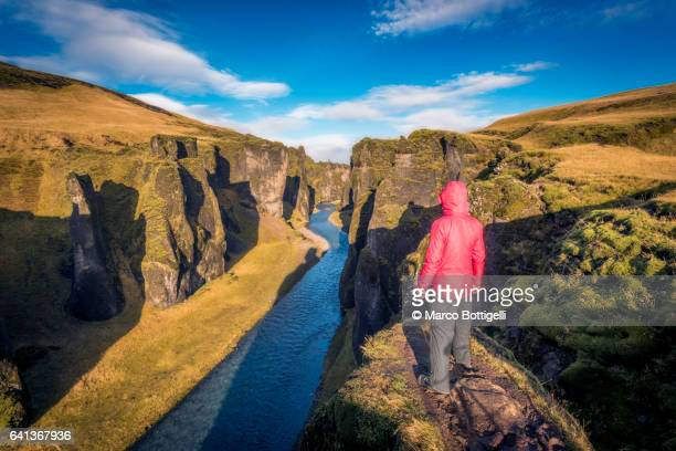 Man with red coat admiring the view of the Fjadrargljufur canyon, Iceland.