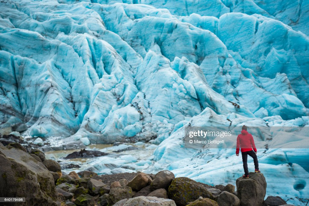 A man with red coat standing on top of a rock admiring the view of a glacier in Skaftafell national park, Eastern Iceland, Northern Europe. : Stock-Foto