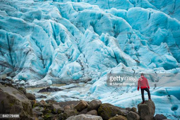 A man with red coat standing on top of a rock admiring the view of a glacier in Skaftafell national park, Eastern Iceland, Northern Europe.