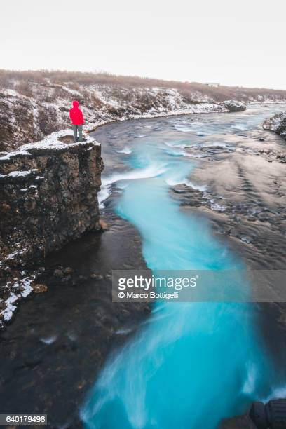 Man with red coat standing on top of the cliff over the blue river of Bruar, Bogarnes, Iceland, Northern Europe.