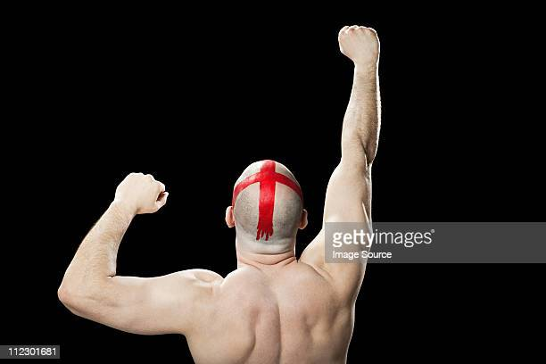 Man with red cross painted on head punching the air