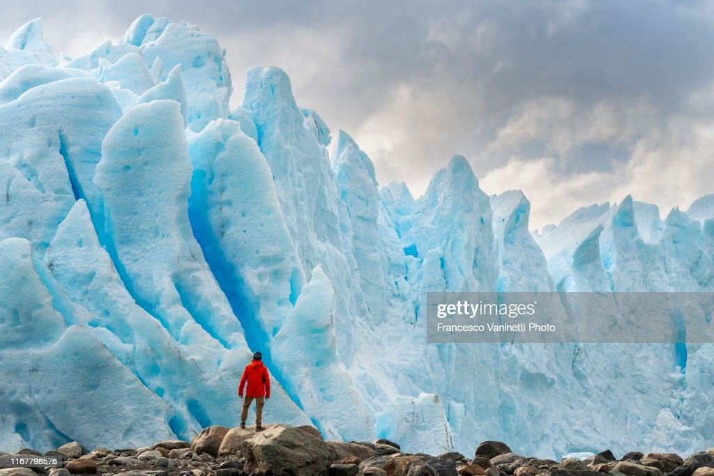 Man with red jacket standing in front of the snout of Perito Moreno glacier, El Calafate, Santa Cruz province, Argentina. : Stock Photo