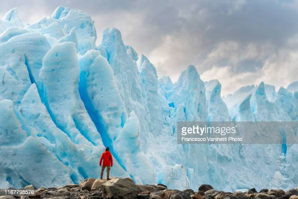man with red jacket standing in front of the snout of perito moreno glacier, el calafate, santa cruz province, argentina. - unesco stock pictures, royalty-free photos & images