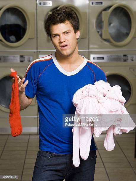 man with red sock and pink clothing at laundromat - pink sock image stock pictures, royalty-free photos & images