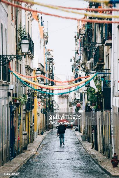 man with red umbrella walking on the streets of lisbon a rainy day, portugal - alfama stock photos and pictures