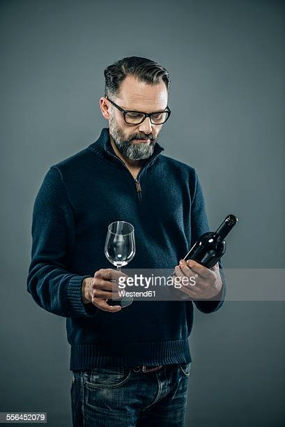 Man with red wine glass and wine bottle