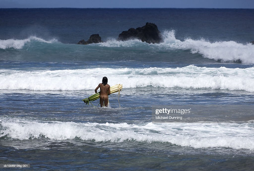 Man with reed surfboard in sea, rear view : Stockfoto