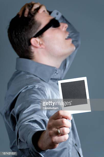 Man with regrets display an instant photo to the camera