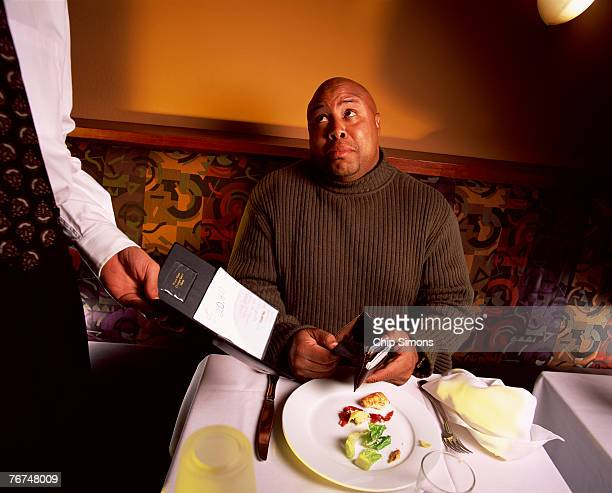 Man with restaurant bill and empty wallet