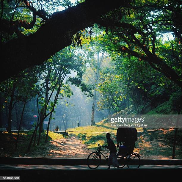 Man With Rickshaw Walking Street By Forest