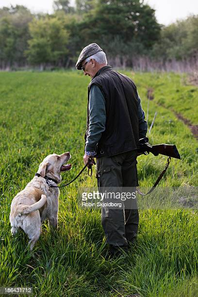 Man with riffle and dog in field