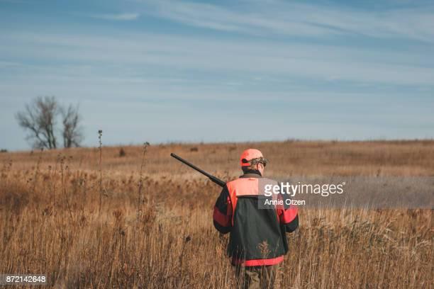 Man with Rifle Walking Through Waist High Prairie Grass
