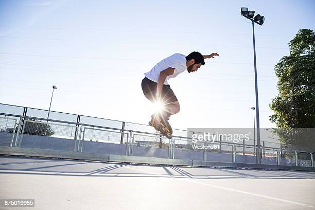 man with rollerblades jumping during a skating session - inline skate stock photos and pictures