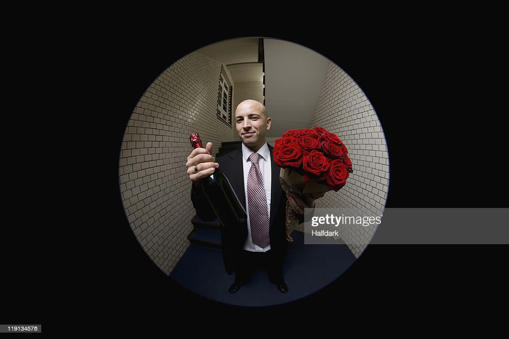 A man with roses and champagne viewed through a peephole : Stock Photo