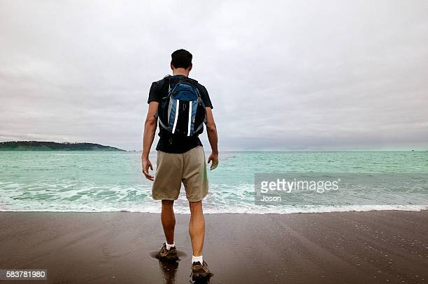 man with rucksack at beach - pantaloncini grigi foto e immagini stock