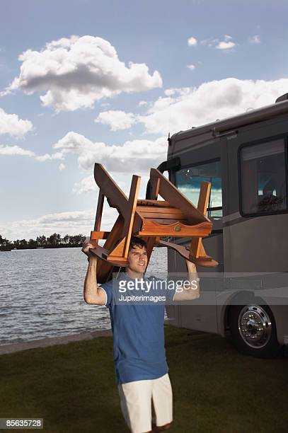 Man with RV carrying chair