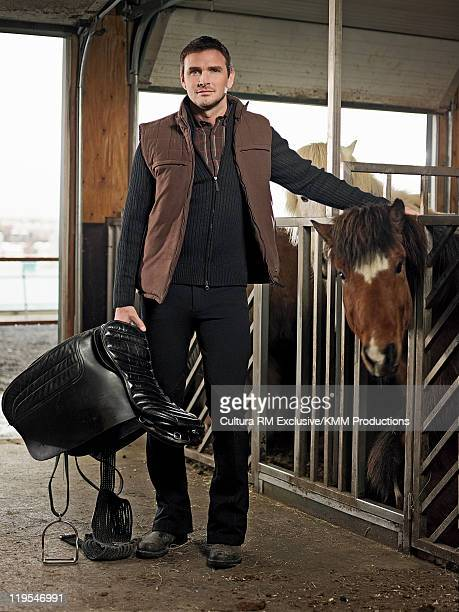 Man with saddle patting horse in stable